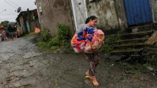 A woman carries cloths as she leaves a mudslide site in Guarujá, São Paulo state, Brazil. Photo: 3 March 2020